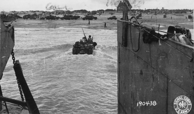 Photo of a jeep driving through water from a landing craft.